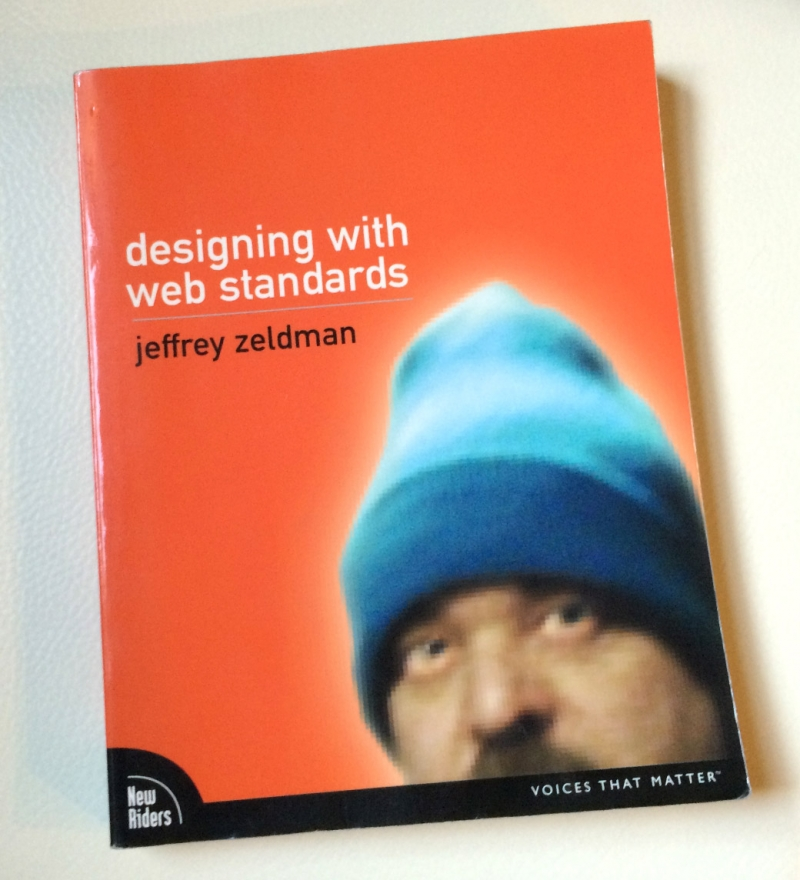 a photo of Jeffrey's book, Designing with Web Standards, showing him wearing the now-famous blue beanie, on an orange cover.